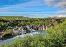 A lava cai corrida de Hraunfossar como cachoeiras e a corredeira minúsculas no rio de Hvita, Borgarfjordur, Islândia ocidental, E foto de stock
