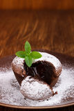 Lava cake with mint. Homemade hot chocolate pudding with fondant centre , lava cake on wooden background royalty free stock photos