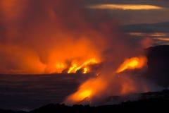 Lava die in de oceaan stroomt Stock Foto