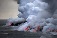 Lava, die in den Ozean fließt stockfotos