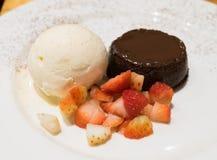 Lava do chocolate, gelado de baunilha e partes da morango Imagem de Stock Royalty Free