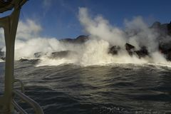 Lava entering the ocean, from touristic boat, Big Island, Hawaii. Lava entering the ocean with steam, as seen from a touristic boat, Big Island, Hawaii Royalty Free Stock Photo