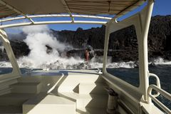 Lava entering the ocean, from touristic boat, Big Island, Hawaii. Lava entering the ocean with steam, as seen from a touristic boat, Big Island, Hawaii Royalty Free Stock Images