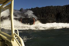 Lava entering the ocean, from touristic boat, Big Island, Hawaii. Lava entering the ocean with steam, as seen from a touristic boat, Big Island, Hawaii Stock Image