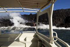 Lava entering the ocean, from touristic boat, Big Island, Hawaii. Lava entering the ocean with steam, as seen from a touristic boat, Big Island, Hawaii Stock Photo