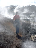 Lava field. A young man wrapped in acid gas coming from the underground cavities on the surface of the earth stock photo