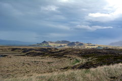 Lava field in Iceland in West fjords area on the background of distant mountains and stormy sky . Stock Photo