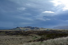 Lava field in Iceland in West fjords area on the background of distant mountains and stormy sky . Stock Image
