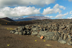 Lava field at Tolbachik volcano, after eruption in 2012 on background Plosky Tolbachik volcano, Klyuchevskaya Group of Stock Image
