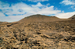 Lava field and volcano. Layers of lava making a field of lava with a volcano in the distance Timanfaya Lanzarote Royalty Free Stock Photos