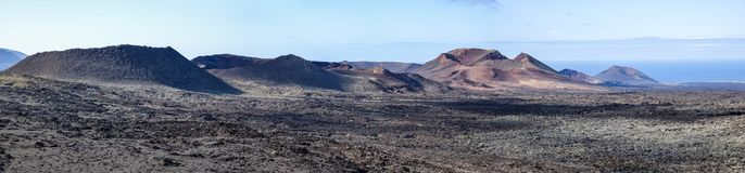 Lava field with volcano caldera. Timanfaya national park. Lanzarote, Canary Islands. Panorama background royalty free stock images