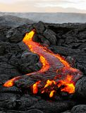 Hawaii - lava emerges from a column of the earth. A lava flow emerges from an earth column and flows in a black volcanic landscape, in the sky shows the first royalty free stock photos
