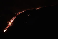 Lava flowing down the mountain. Molten lava flowing down the side of a mountain Royalty Free Stock Images