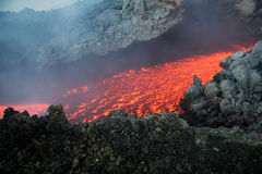 Lava flowing down mountainside. Scenic view of red hot lava flowing down volcanic mountainside Stock Photos