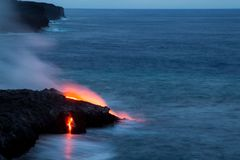 Lava flowing into the sea. Red glowing lava flowing into the sea in the Hawaii Volcanoes National Park on Big Island, Hawaii, USA Royalty Free Stock Photos