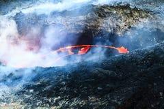 A lava incandesce cratera interna cercada pelo fumo e pelos gáss fotos de stock