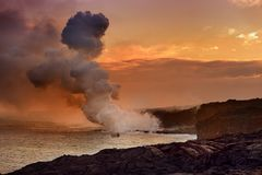 Lava pouring into the ocean creating a huge poisonous plume of smoke at Hawaii`s Kilauea Volcano, Volcanoes National Park, Hawaii. Lava pouring into the ocean Royalty Free Stock Photography