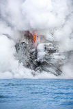 Lava pouring into the ocean in Hawaii. A lava flow on the big Island of Hawaii known as the fire hose spews out molten magma from Kilauea Volcano into the ocean Stock Image