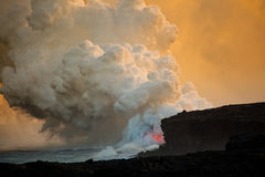 Lava que entra no oceano no por do sol Fotografia de Stock Royalty Free