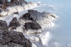Lava Rock in Blue Lagoon Royalty Free Stock Photography