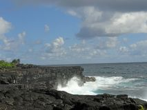 Lava Rock Cliffs embrace the Turquoise Ocean on the big island of Hawaii Stock Image