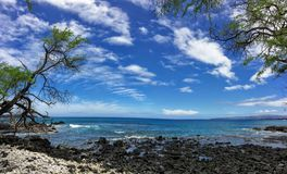 Lava Rock and Coral with Spray of crashing wave in tide pools at Maluaka Beach and Kihei Maui with sky and clouds Stock Photo