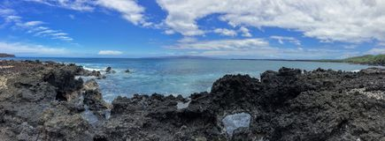 Lava Rock and Coral with Spray of crashing wave in tide pools at Maluaka Beach and Kihei Maui with sky and clouds Royalty Free Stock Images