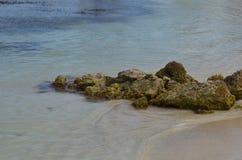 Lava Rock dégringolé sur la plage dans Aruba Image libre de droits