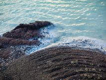 Lava Rock at the Edge of Blue Water Royalty Free Stock Photography