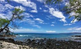 Lava Rock och korall med sprej av att krascha vågen i tidvattentips på Maluaka sätter på land och Kihei Maui med himmel och moln Arkivfoto