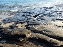 Lava rock, sand, and waves at the beach Stock Photography