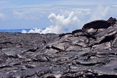 Lava Rock and Smoke. Lava rock forming new land on the big island of Hawaii. In the distance is the smoke and steam rising from the lava flowing into the Pacific royalty free stock photo