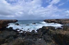 Lava Rock Surrounding een Inham op de Kustlijn van het Oosten van Aruba ` s royalty-vrije stock foto's