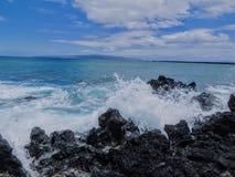 Lava Rock und Koralle mit Spray der zusammenstoßenden Welle in den Gezeitenpools an Maluaka-Strand und Kihei Maui mit Himmel und  lizenzfreies stockbild