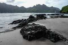 Lava rocks on shoreline with mountains in background, Nuku Hiva, Marquesas Islands, French Polynesia Royalty Free Stock Photos