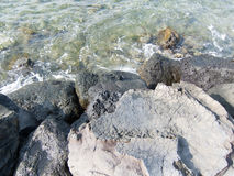 Lava Rocks in the Surf. Lava rocks with shallow water Stock Images