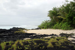 Lava on the sand beach Royalty Free Stock Photography