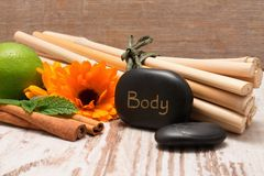 Lava stone with the inscription BODY, bamboo and marigold Stock Photos