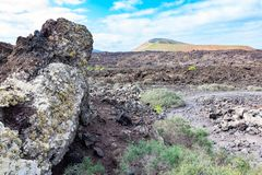 Lava stone and tourist road trail to vulcano Caldera Blanca, Lanzarote, Canary Islands, Spain.  stock image