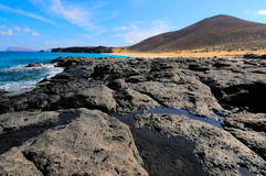 Lava stream and ancient volcano. Graciosa, Spain. A view of an ancient lava stream that have reacher the shore of Atlantic Ocean. Las Conchas bay, northern Stock Photography