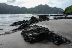 Lava vaggar på shoreline med berg i bakgrund, Nuku Hiva, Marquesas öar, franska Polynesien Royaltyfria Foton
