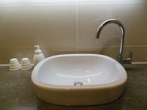 Lavabo avec le robinet, le distributeur de savon et les tasses photos stock