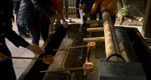 Lavabo de lavado tradicional de la mano con las cucharones en un templo en Kyoto almacen de video