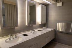 Lavabo de mármol de lujo con la luz en espejo en retrete público fotografía de archivo