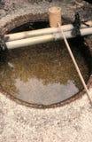Lavabo del agua con la cuchara de bambú Fotos de archivo libres de regalías
