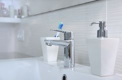 Lavabo en el cuarto de baño, el dispensador del jabón y el cepillo de dientes blancos en un vidrio imagenes de archivo