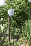 Lavabo manual del metal en arbustos de frambuesa en la yarda de una casa de campo vieja imágenes de archivo libres de regalías