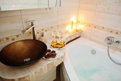 Lavabo moderne dans la salle de bains avec les bougies brûlantes Photographie stock