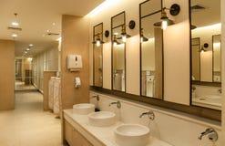 Lavabo vacío público del hombre con los espejos de los lavabos en los grandes almacenes centrales fotografía de archivo
