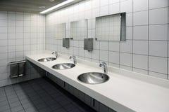 Lavabos blancs brouillés et robinets brillants dans la toilette avec la fusée Photographie stock libre de droits